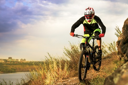 Professional Cyclist Riding the Bike at the Rocky Trail. Extreme Sport Concept. Free Space for Text. Stock Photo