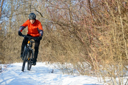 Mountain Biker Riding Bike on the Snowy Trail in the Beautiful Winter Forest