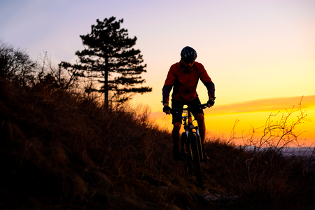 Silhouette of Enduro Cyclist Riding the Mountain Bike on the Rocky Trail at Sunset. Active Lifestyle Concept. Free Space for Text. Stock Photo
