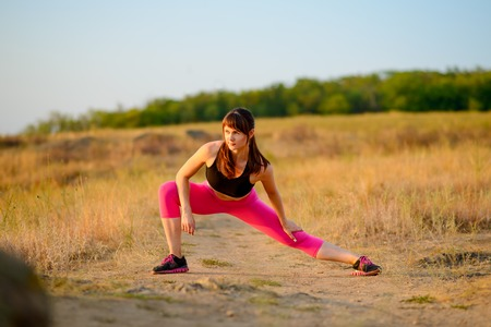 Young Fitness Woman Stretching in the Wild Park. Female Runner Doing Stretches Outdoor. Healthy Lifestyle Concept. Stock Photo