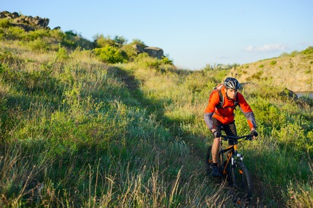 red mountain: Cyclist in Red Jacket Riding the Mountain Bike on the Beautiful Spring Trail. Travel and Adventure Sport Concept