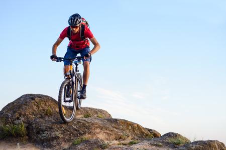 Fietser in rood T-shirt rijden op de fiets langs de rots op de blauwe hemelachtergrond. Extreme sport en enduro fietsen concept.