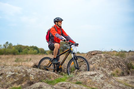 Happy Cyclist in Red Resting on the Bike on the Rocky Trail. Adventure Sport and Travel Biking Concept.
