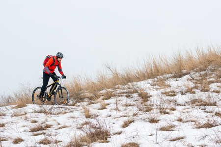 Cyclist in Red Riding the Mountain Bike on the Snowy Trail. Extreme Winter Sport and Enduro Biking Concept. Stock Photo