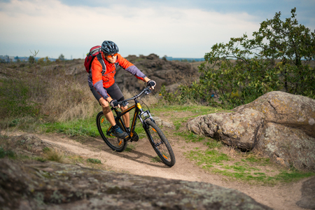 Cyclist in Red Riding the Bike on the Autumn Rocky Trail. Extreme Sport and Enduro Biking Concept.