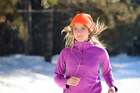 Young Woman Running in the Beautiful Winter Forest at Sunny Frosty Day. Active Lifestyle Concept. Stock Photo