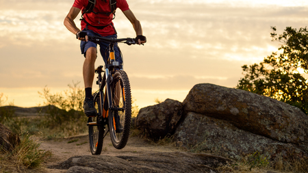 Cyclist in Red T-Shirt Riding the Bike on the Rocky Trail at Sunset. Extreme Sport and Enduro Biking Concept.