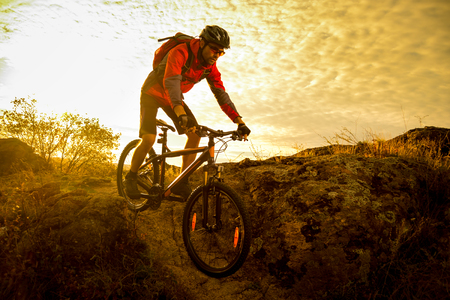 Cyclist in Red Riding the Bike on Autumn Rocky Trail at Sunset. Extreme Sport and Enduro Biking Concept. Stok Fotoğraf