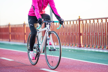 Young Woman in Pink Jacket Riding Road Bicycle on the Bridge Bike Line in the Cold Sunny Autumn Day. Healthy Lifestyle. Archivio Fotografico