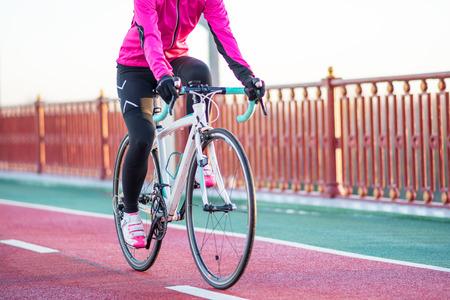 Junge Frau im rosa Jacken-Reitstraßen-Fahrrad auf der Brücken-Fahrrad-Linie am kalten sonnigen Herbst-Tag. Gesunder Lebensstil.