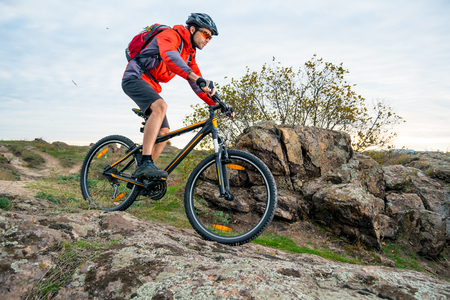 Cyclist in Red Riding the Mountain Bike down the Autumn Rocky Trail. Extreme Sport and Enduro Biking Concept.