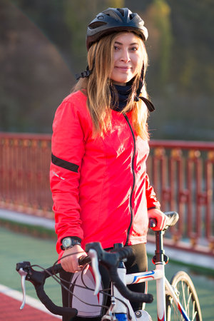 Portrait of Young Smiling Female Cyclist in Bright Orange Jacket Resting with Road Bicycle in the Cold Sunny Autumn Day. Healthy Lifestyle Concept.