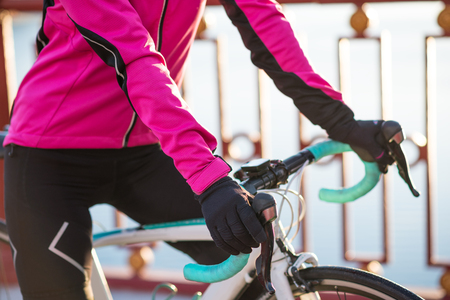 Close up Photo of Female Cyclist Hands in the Warm Gloves on the Road Bicycle Handlebar in the Cold Sunny Autumn Day. Healthy Lifestyle Concept.