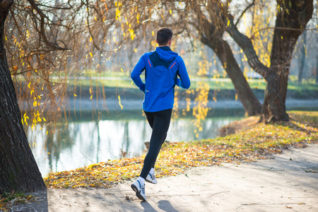 Young Sports Man Running in the Park in Cold Sunny Autumn Morning. Healthy Lifestyle and Active Sport Concept.