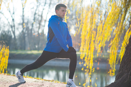 Young Male Runner Stretching in the Park in Cold Sunny Autumn Morning. Healthy Lifestyle and Active Sport Concept. Stock Photo