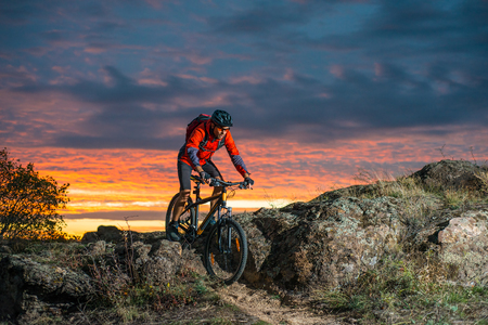 Cyclist in Red Riding the Bike on Autumn Rocky Trail at Sunset. Extreme Sport and Enduro Biking Concept. Stock Photo