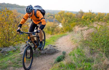 Ciclista em Orange Andar de bicicleta de montanha no Outono Rocky Trail. Esporte radical e Enduro Biking Concept. Foto de archivo