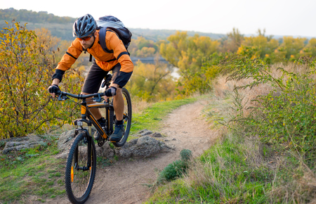 Cyclist in Orange Riding the Mountain Bike on the Autumn Rocky Trail. Extreme Sport and Enduro Biking Concept. Фото со стока