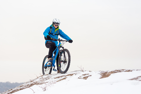 Cyclist in Blue Riding the Mountain Bike on the Rocky Winter Hill Covered with Snow. Extreme Sport and Enduro Biking Concept. Stock Photo