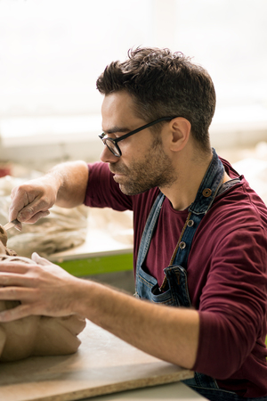 Ceramist Dressed in an Apron Sculpting Statue from Raw Clay in Bright Ceramic Workshop. Stock Photo