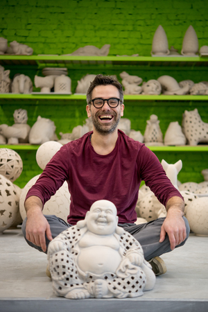 Portrait of Smiling Young Ceramist in the Bright Modern Ceramic Workshop Sitting Next to his Sculpture. Small Business Concept.