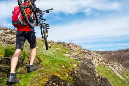 Enduro Cyclist Taking his Mountain Bike up to Beautiful Rocky Trail. Extreme Sport and Adventure Concept.