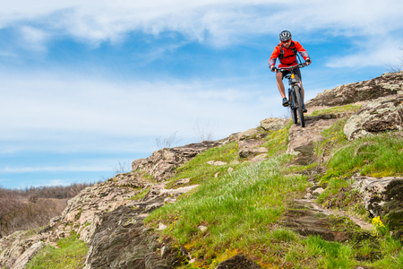 Cyclist in Red Jacket Riding Mountain Bike Down Rocky Hill. Extreme Sport and Adventure Concept. Zdjęcie Seryjne