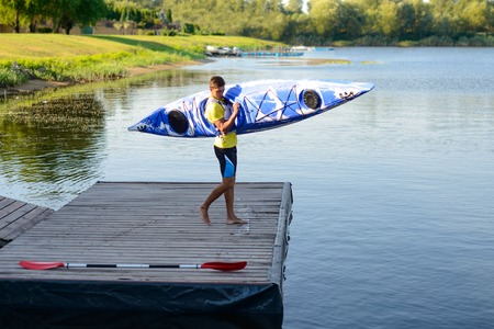 Young Professional Kayaker Getting Ready for Morning Kayak Training on the River. Sport and Active Lifestyle Concept