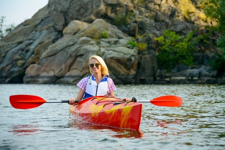 Young Woman Paddling Kayak on the Beautiful River or Lake among Stones at the Evening Stock Photo