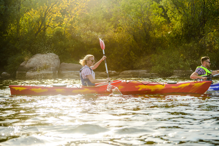 Young Happy Couple Paddling Kayaks on the Beautiful River or Lake Stock Photo