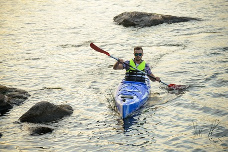 Man Paddling Kayak on Beautiful River or Lake among Stones at the Evening