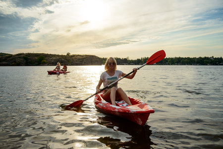 Young Happy Woman Paddling Kayaks on the Beautiful River or Lake under Dramatic Evening Sky at Sunset