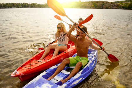 Friends Having Fun on Kayaks on the Beautiful River or Lake at Sunset Stock Photo