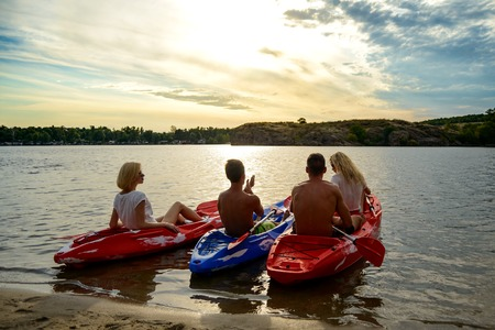 Friends Resting and Talking while Sitting in Kayaks on the Beautiful River or Lake Beach under the Dramatic Evening Sky at Sunset Stock Photo