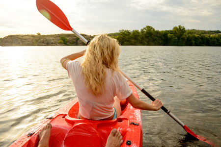 Young Woman Paddling Kayak on the Beautiful River or Lake at Sunset. Back View from the Second Place in the Boat. Stock Photo