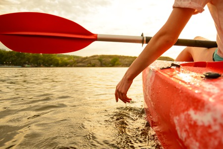 Young Woman Playing with Water while Sitting in Kayak on the Beautiful River or Lake at Sunset. Close up view of Female Hand.