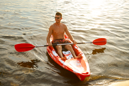 Young Happy Man Paddling Kayak on the Beautiful River or Lake at Sunset
