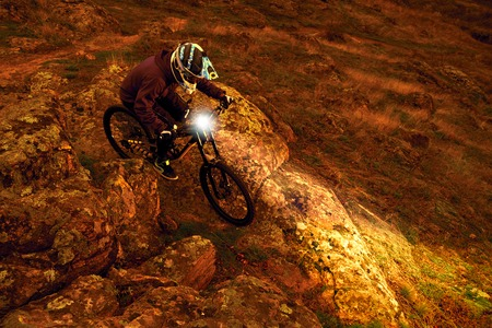 Professional Cyclist Riding the Mountain Bike Down the Rocky Hill at Night with Flashlight. Extreme Sport and Enduro Biking Concept.