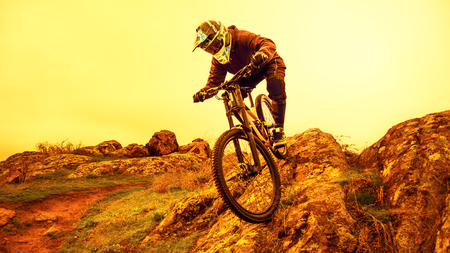Professional Cyclist Riding the Mountain Bike Down the Rocky Hill. Extreme Sport and Enduro Biking Concept.