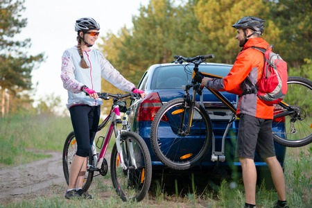 Young Couple Unmounting Mountain Bikes from Bike Rack on the Car. Adventure and Family Travel Concept. Stock Photo