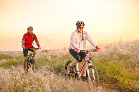 Young Couple Riding the Mountain Bikes in the Beautiful Field Full of Feather Grass at Sunset. Adventure and Family Travel Concept. Stock Photo