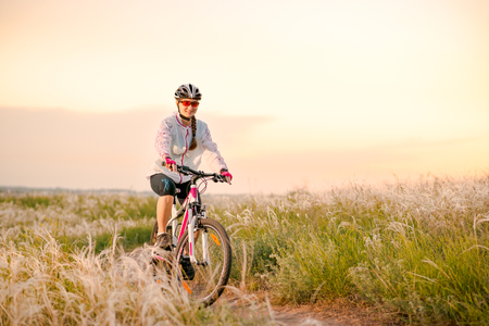 Young Woman Riding the Mountain Bikes in the Beautiful Field Full of Feather Grass at Sunset. Adventure and Travel Concept.