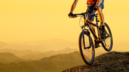 Cyclist Riding the Bike in the Beautiful Mountains Down the Rock on the Sunset Sky Background. Extreme Sport and Enduro Biking Concept.
