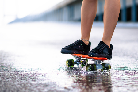 Close up of Young Girl`s Legs Riding Orange Skateboard on the Wet Road in the Rain