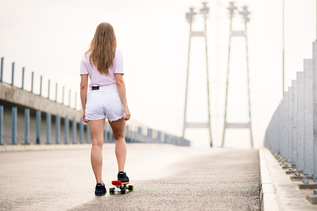 Young Beautiful Blonde Girl Riding Orange Skateboard on the Bridge Imagens