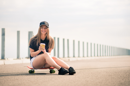 Young Beautiful Smiling Blonde Girl Drinking Coffee while Sitting on the Skateboard on the Bridge