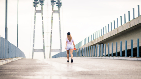 Young Blonde Girl Walking Away with Orange Skateboard on the Bridge
