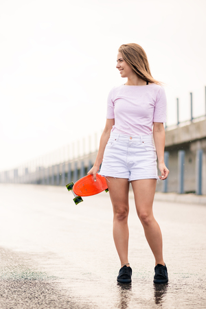 Young Beautiful Blonde Girl with Bright Skateboard on the Bridge