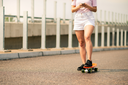 Young Girl Using Smartphone on the Skateboard. Close up Photo