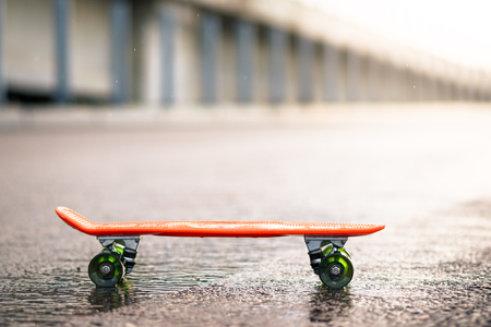 Close up of Orange Skateboard on the Wet Road in the Rain